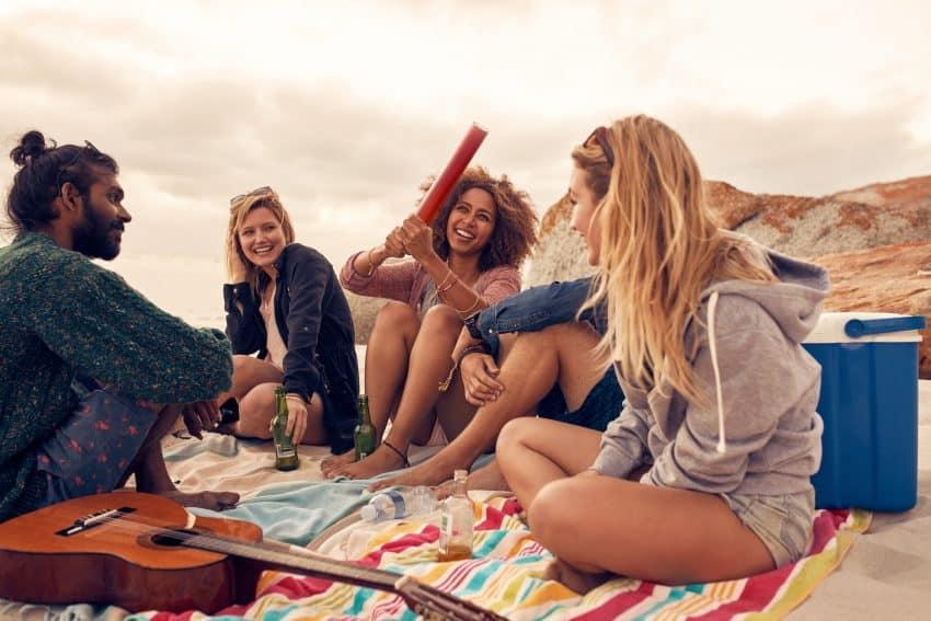 Amigos bebendo e tocando violão na praia