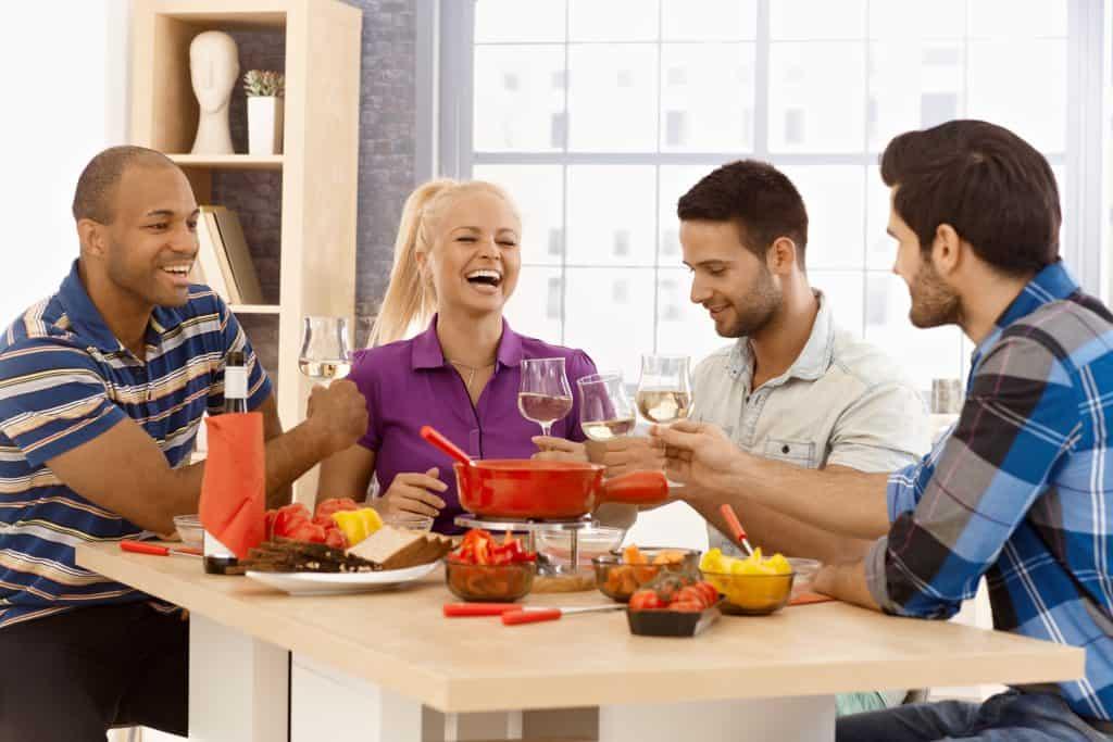 quatro pessoas sentados à mesa comendo fondue e bebendo vinho