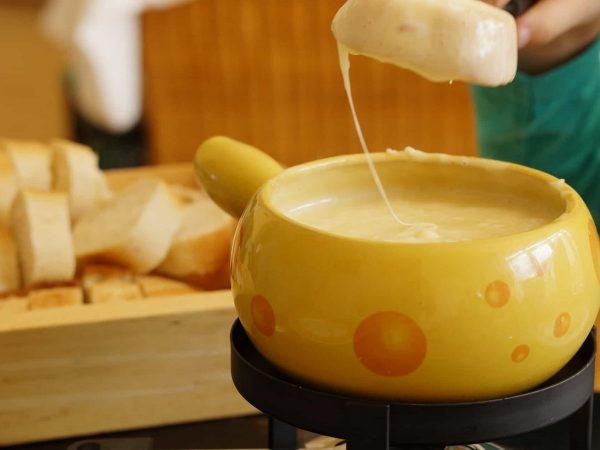 Pão mergulhado em fondue de queijo servido em panela de cerâmica.