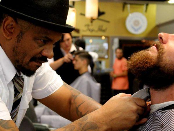 Imagem mostra homem barbeando outro em uma barbearia usando um barbeador elétrico.