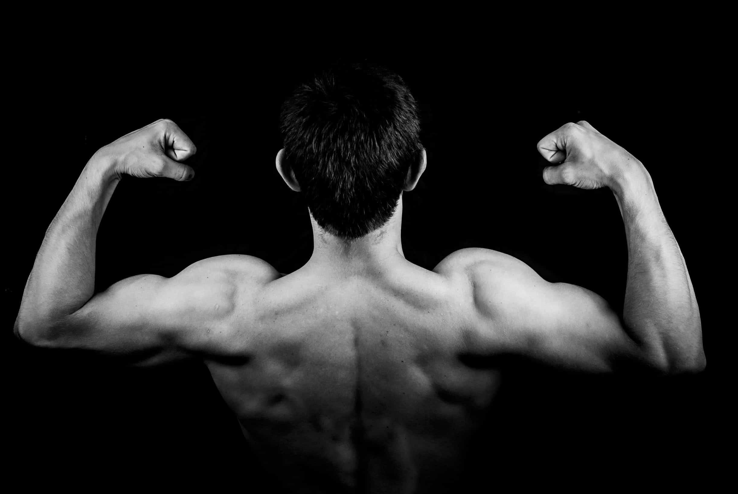 homem de costas forçando o bíceps, de forma a parecer forte
