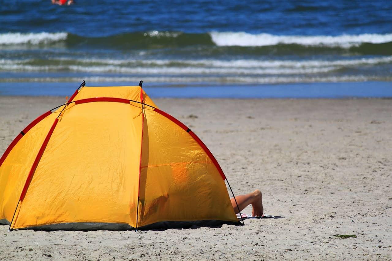 Imagem mostra uma barraca na areia da praia.