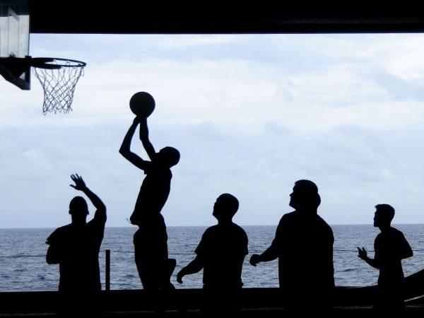 Silhueta de pessoas jogando com uma bola de basquete em frente ao mar.
