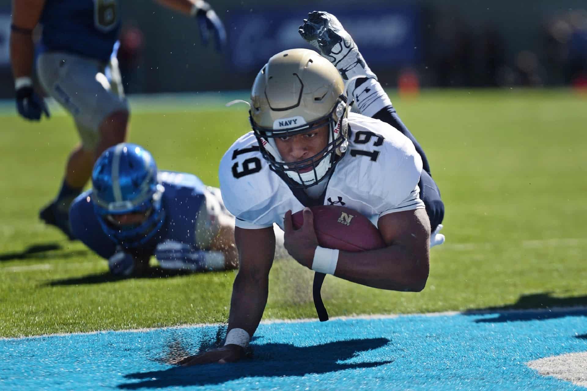 Jogador caindo com a bola de futebol americano
