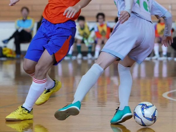 dois jogadores de futsal em close disputando a bola