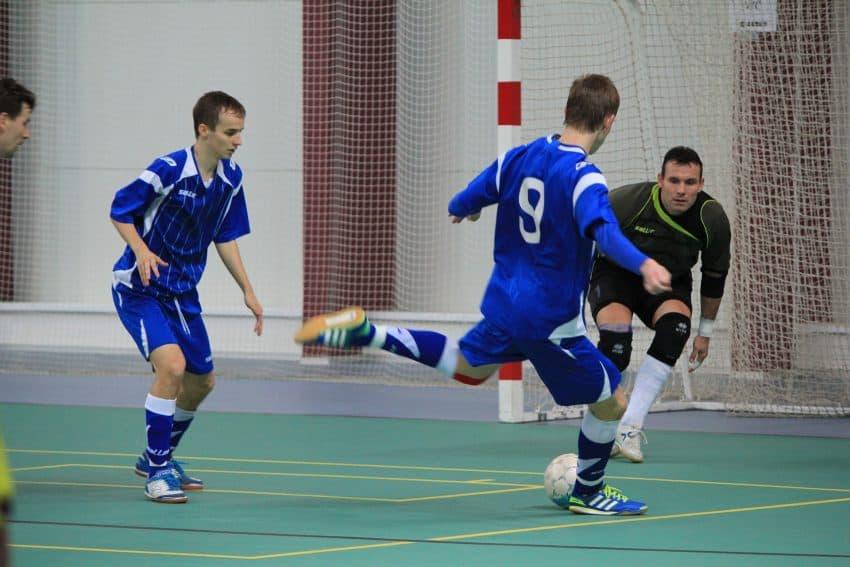 homem chutando bola de futsal no gol
