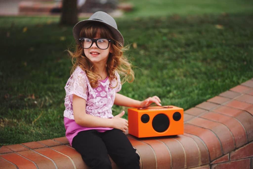 Menina manuseando uma caixa de som bluetooth de cor laranja e estilo retrô