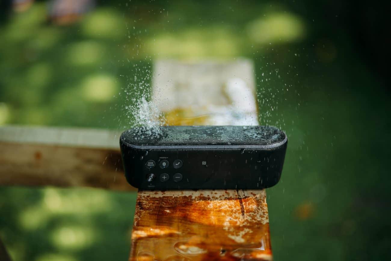 imagem mostra uma caixa de som bluetooth em uma bancada de madeira
