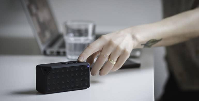 mão apertando botão em caixa de som Bluetooth