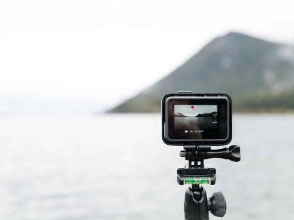 Uma câmera de ação está posicionada em um tripé para fotografar a paisagem que está à sua frente.