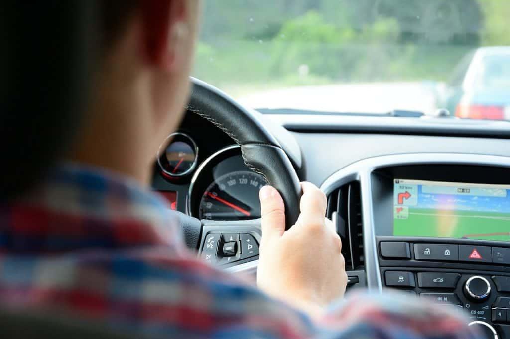 Homem ao volante com DVD em modo de navegação.