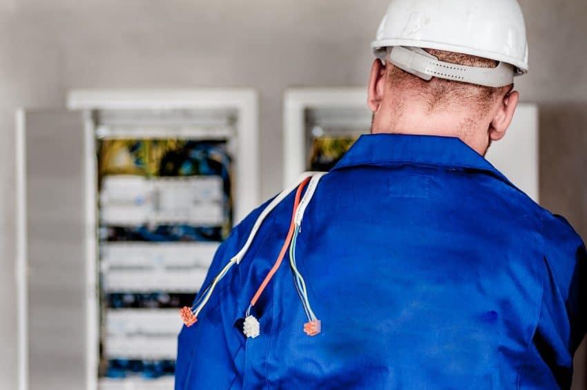 Imagem mostra eletricista de costas, com fios nos ombros.
