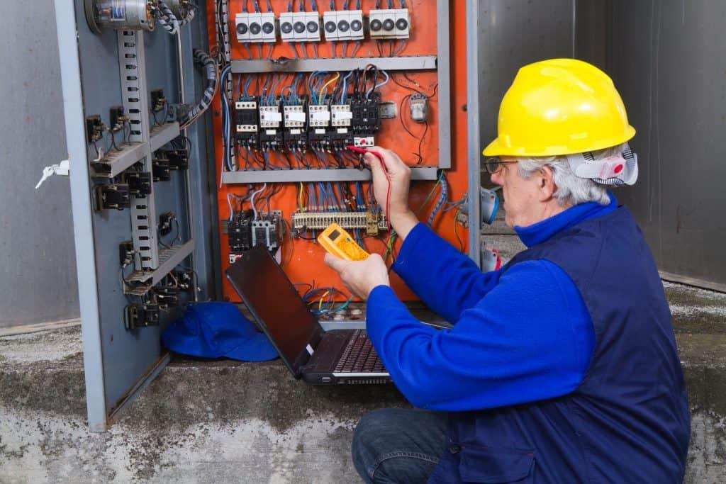 Eletricista trabalhando em um painel usando alicate amperímetro