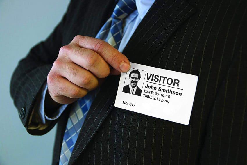 Imagem mostra mão em close segurando etiqueta que diz: visitor.