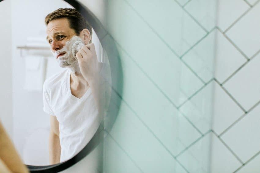 Imagem mostra homem fazendo a barba em frente ao espelho.