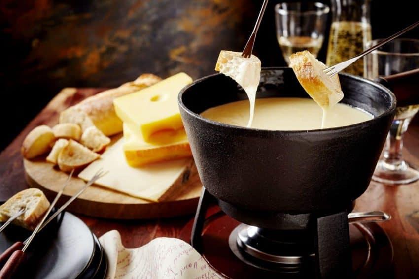 Imagem mostra fondue de queijo com pão.