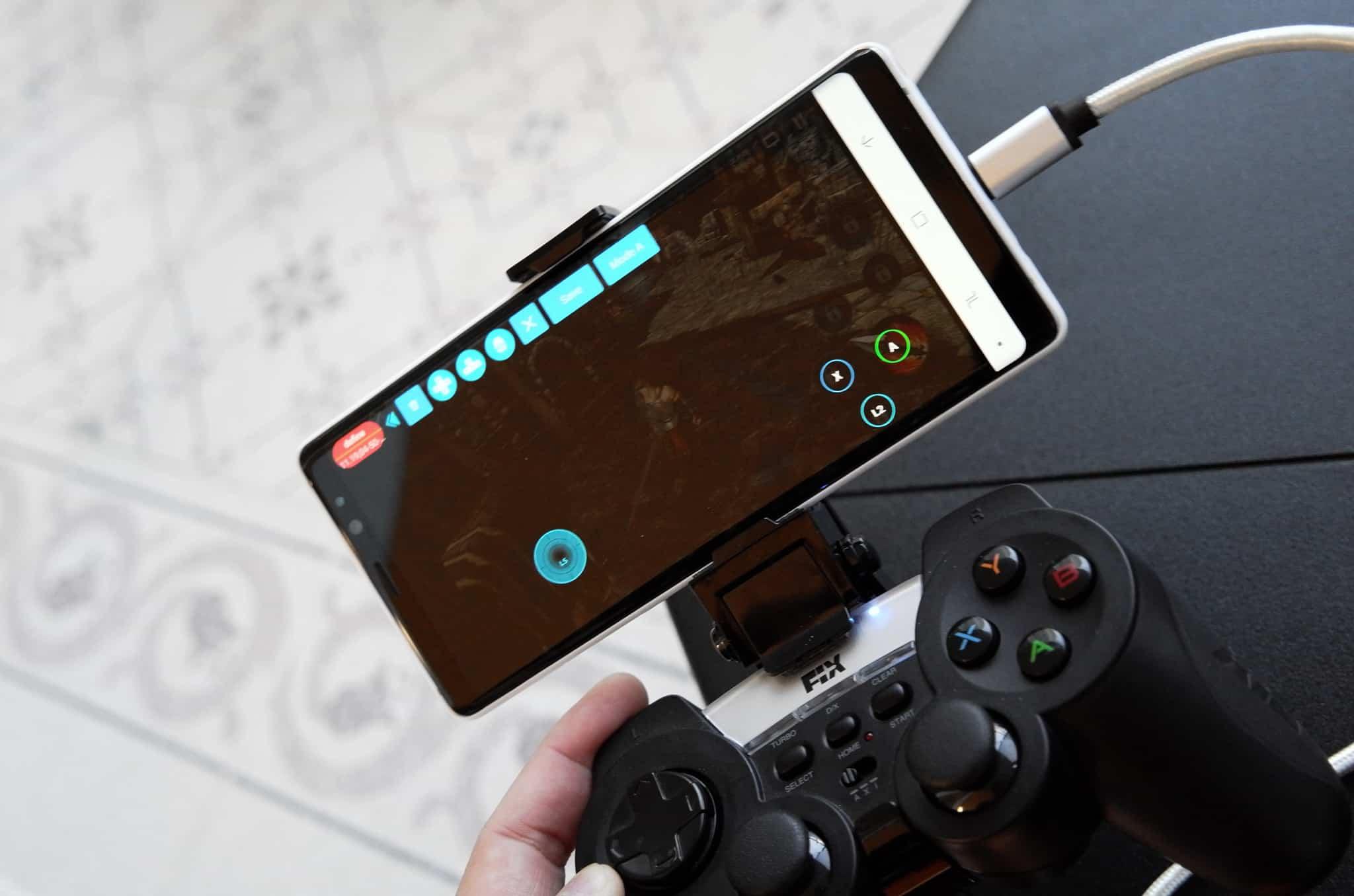 Imagem mostra uma mão segurando um gamepad com um smartphone acoplado.