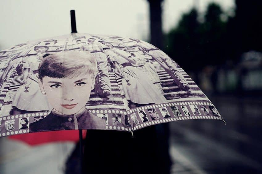 Imagem mostra guarda chuva com cobertura estampada na qual aparece a imagem de uma mulher.