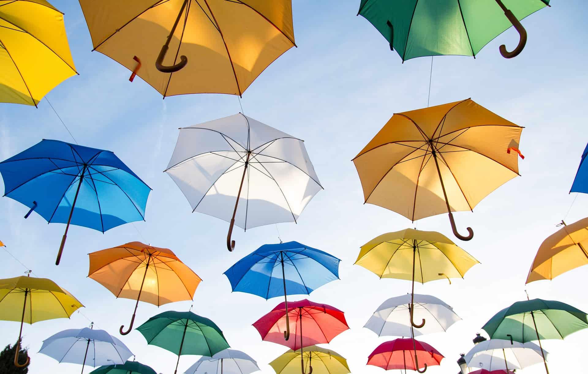 Imagem mostra alguns guarda-chuvas coloridos abertos.