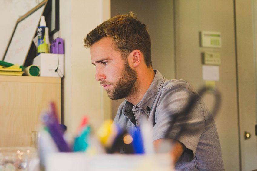 Imagem mostra homem de barba aparada em frente a um computador.