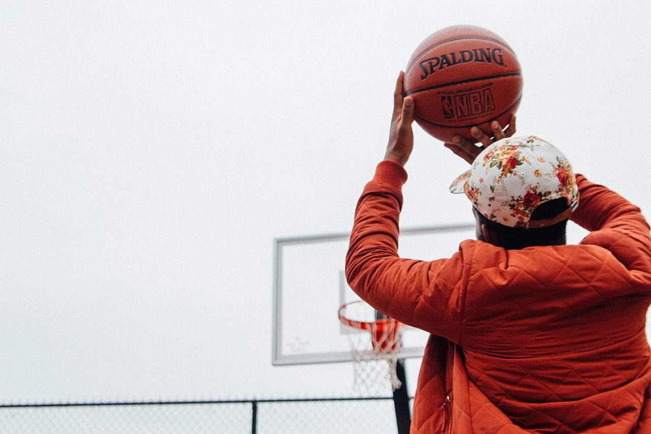 Menino arremessando uma bola de basquete em direção a cesta em uma quadra outdoor.