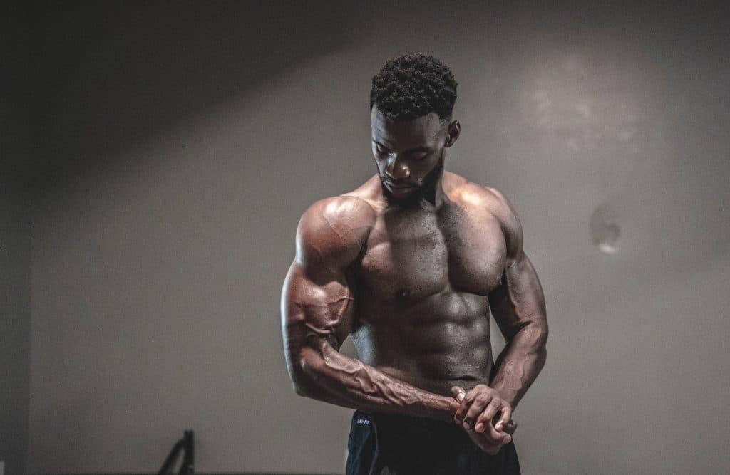 Homem de frente, sem camisa, olhando para o braço e fazendo força