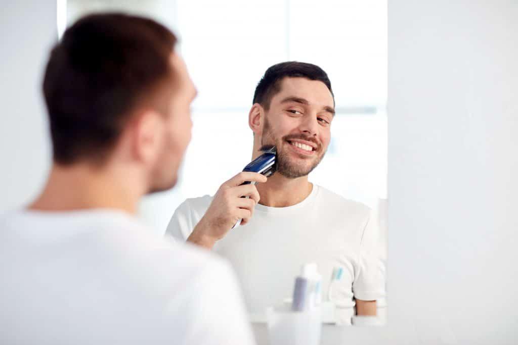 homem fazendo a barba com barbeador elétrico na frente do espelho