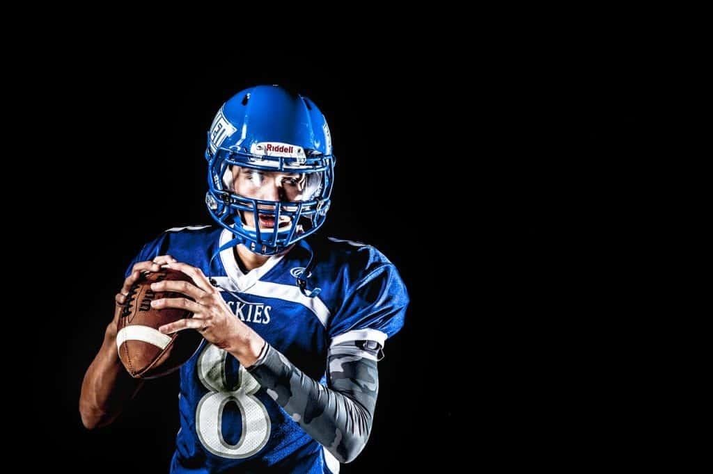 Imagem mostra jogador profissional segurando uma bola de futebol americano e preparando-se para o arremesso.