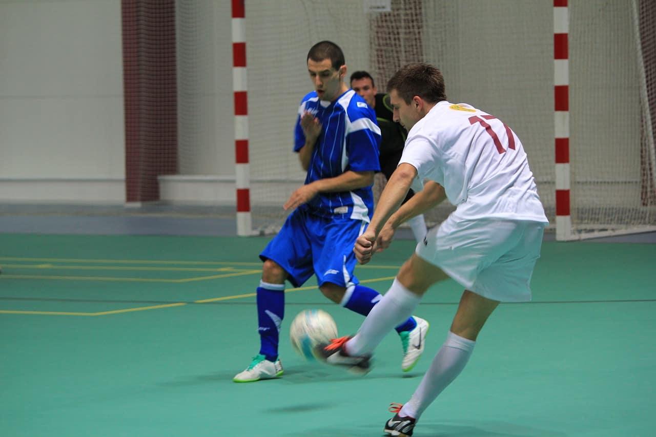 Jogador de uniforme branco chutando bola de futsal enquanto jogador de uniforme azul se defende.