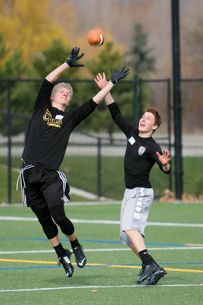 Imagem mostra dois jovens treinando ou se divertindo com uma bola de futebol americano.