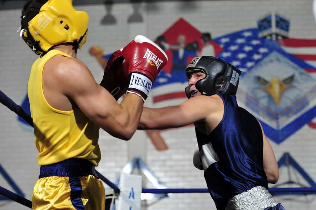 Imagem contém dois boxeadores lutando em um ringue