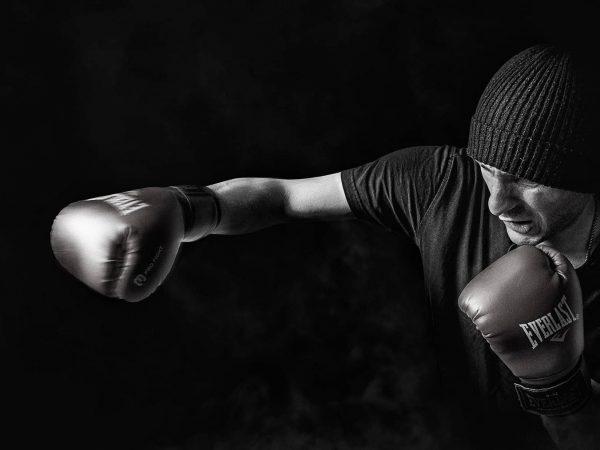 Imagem mostra lutador praticando golpes com luvas de boxe