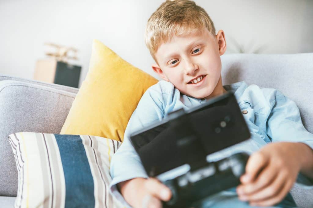 menino sentando no sofá jogando com seu celular e gamepad
