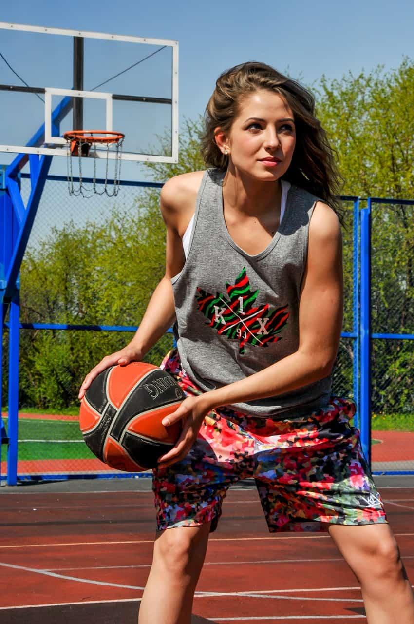 Garota segurando bola de basquete em quadra de rua / Tamanho, gênero e ambiente são fatores a serem analisados para a escolha de sua bola de basquete.