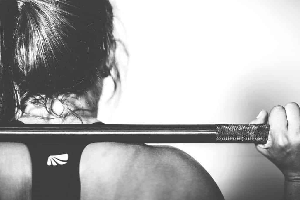 Mulher de costas, segurando uma barra nos ombros