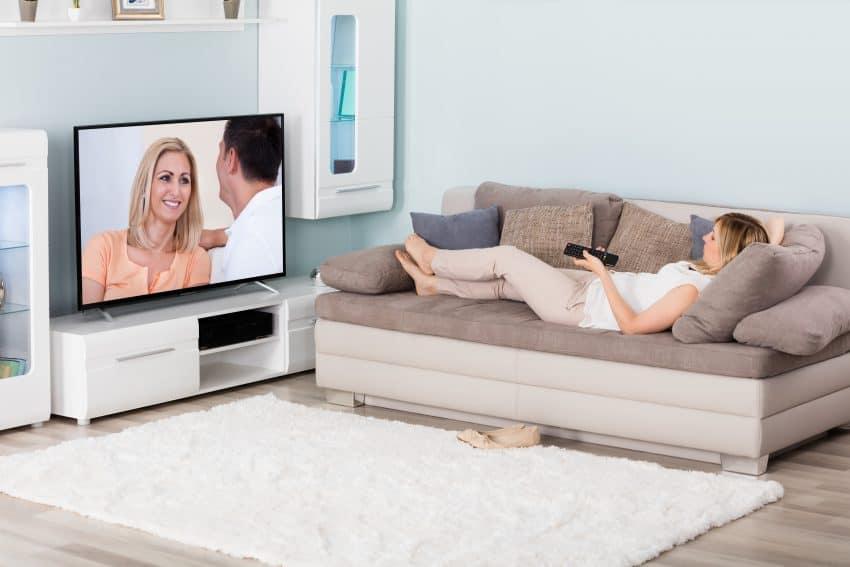 mulher assistindo TV deitada no sofá da sala com controle na mão
