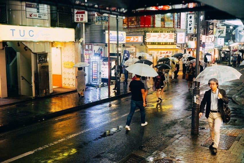 pessoas andando na rua em dia de chuva à noite