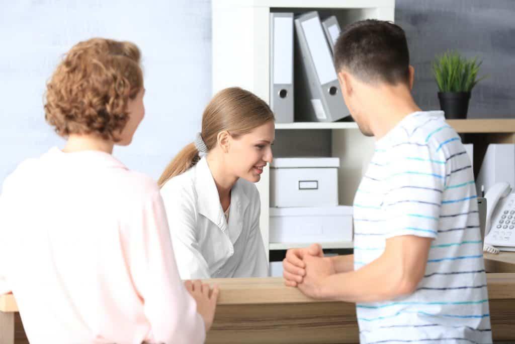 Recepcionista olhando para o computador enquanto dois clientes aguardam no balcão