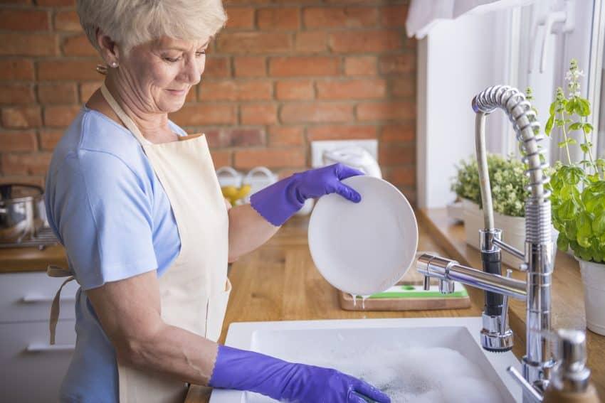 senhora lavando louça com luva em uma pia grande com torneira gourmet