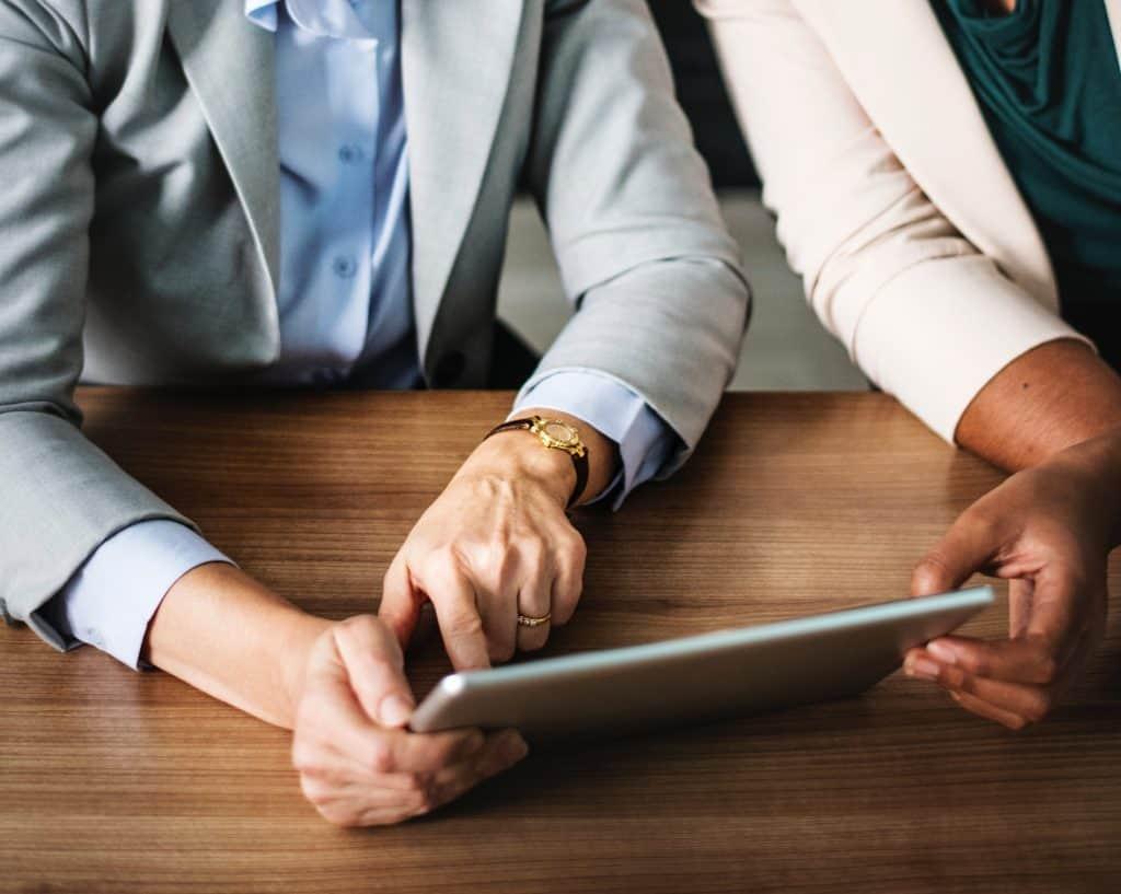 imagem em close mostra os braços de duas pessoas segurando um tablet