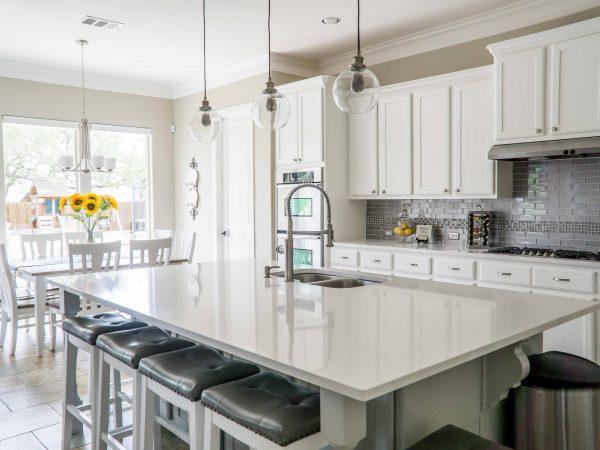 Imagem mostra cozinha moderna com torneira gourmet na bancada.