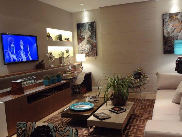 Imagem mostra sala com uma televisão ao lado esquerdo.