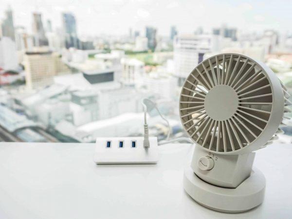 Imagem mostra ventilador USB branco com cidade ao fundo.