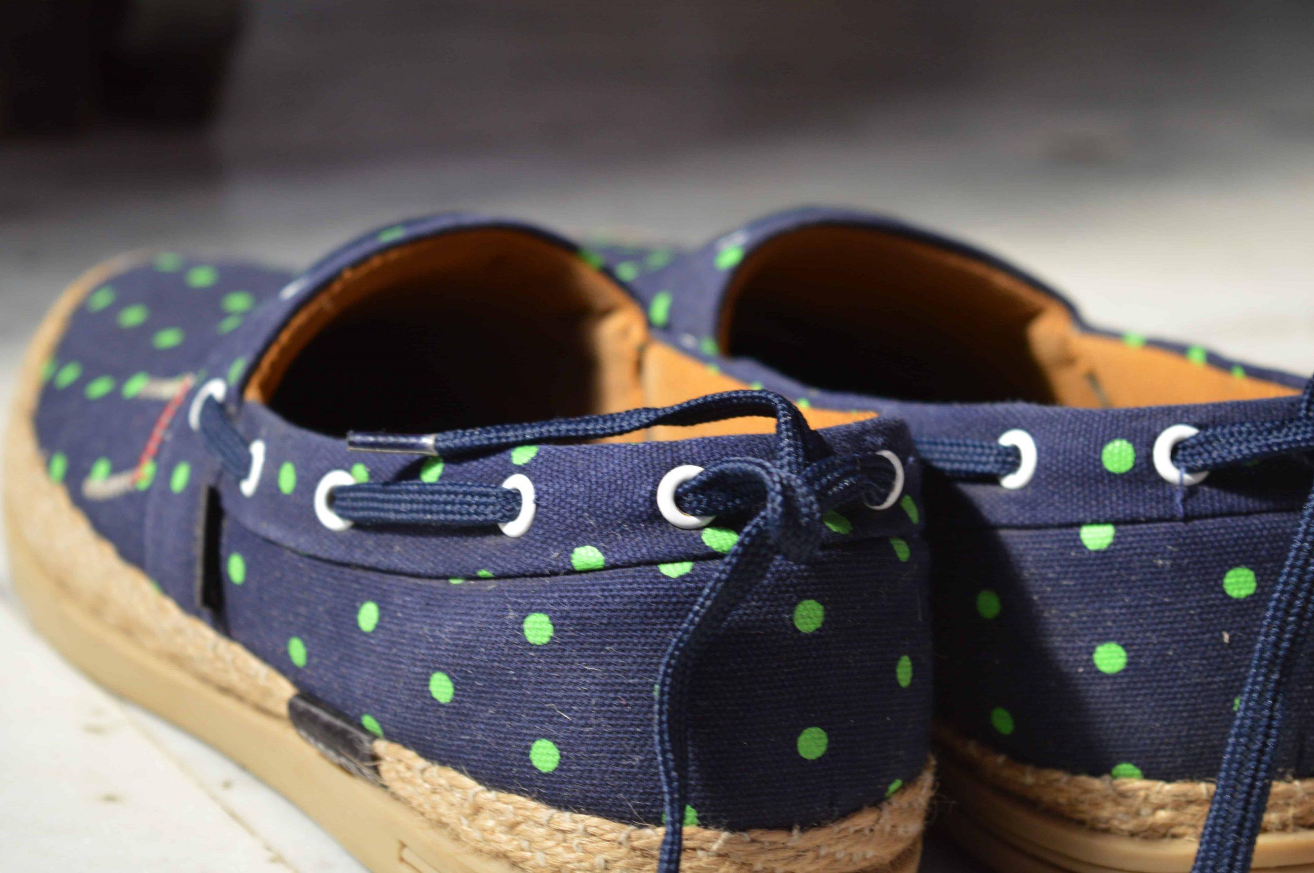 Imagem mostra um par de alpargatas azuis com bolinhas verdes.