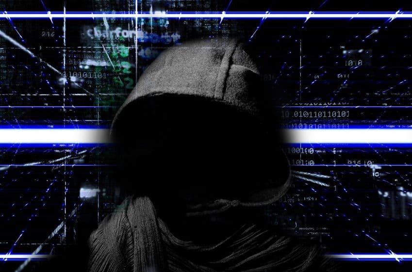 Imagem mostra pessoa com moletom e capuz preto, com rosto indecifrável. Fundo com motivos tecnológicos.