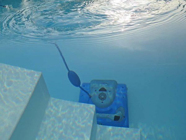 Imagem mostra um aspirador automático no fundo de uma piscina.