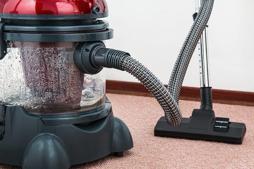 Imagem de aspirador de pó e água realizando a limpeza de tapete.