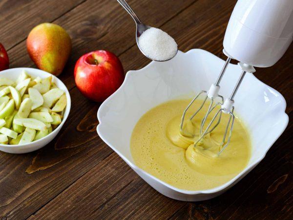 Imagem mostra uma batedeira de mão sendo utilizada no preparo de uma receita com açúcar e frutas.