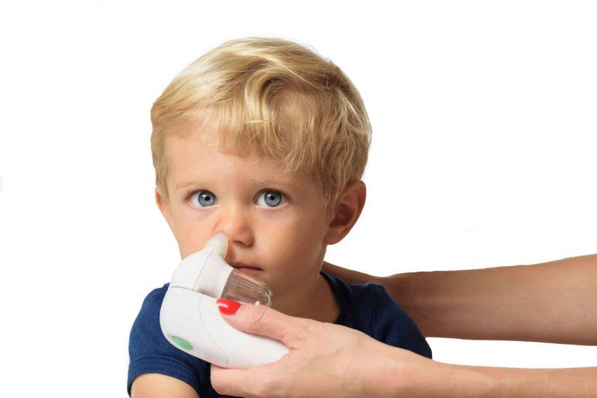 Imagem mostra criança maior de 2 anos de idade aspirando o nariz com aspirador nasal elétrico.