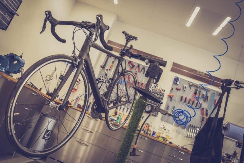 Imagem mostra oficina de bicicleta, com uma bicicleta ao lado de uma bomba de piso e uma mangueira em primeiro plano. Ao fundo, ferramentas diversas na parede, acima de um gaveteiro.